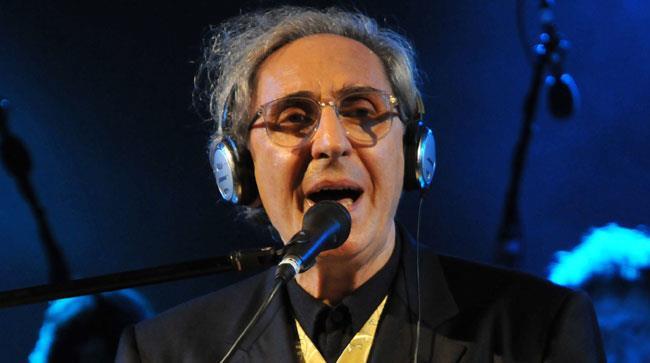 Franco Battiato con le cuffie canta sul palco