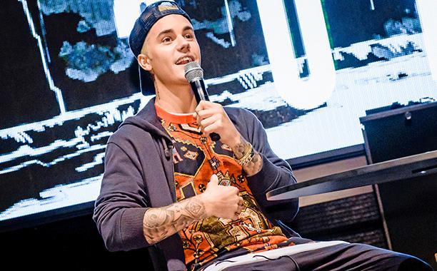 Justin Bieber seduto con il microfono in mano