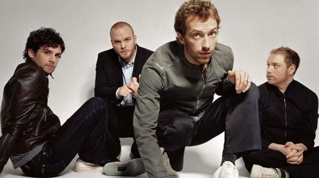 I componenti dei Coldplay seduti per terra