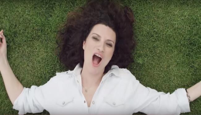 Laura Pausini stesa sull'erba nel video di Simili