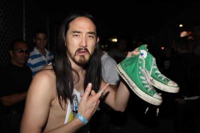 Il DJ Steve Aoki con un paio di Converse in mano