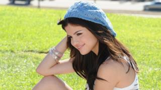 Selena Gomez in un prato con un cappellino azzurro