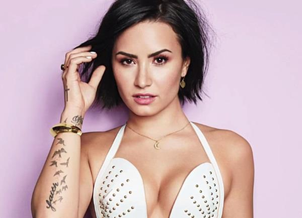 Demi Lovato con reggiseno di pelle bianca e bracciale dorato