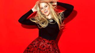 Meghan Trainor balla con le mani alzate su uno sfondo rosso