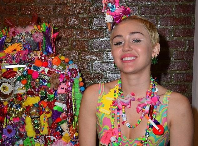Miley Cyrus di fianco alla sua opera d'arte multicolor