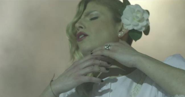 Emma con vestito bianco e fiore tra i capelli