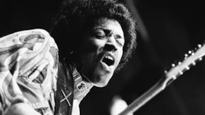 Immagine in bainco e nero di Jimi Hendrix con la chitarra in mano ad un concerto negli anni '60