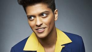 Bruno Mars in giacca blu e camicia gialla
