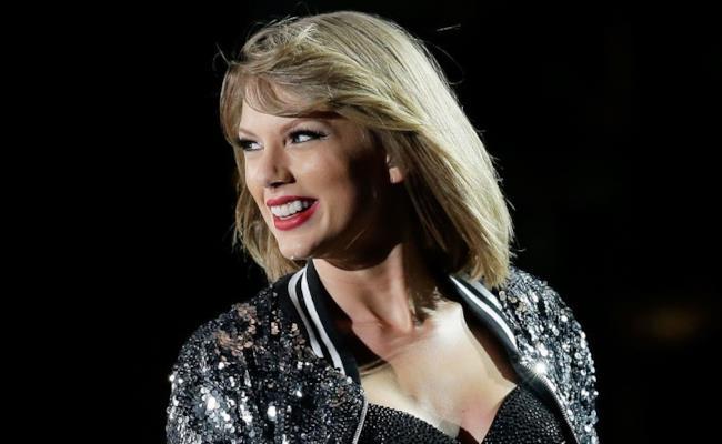Taylor Swift sorridente sul palco durante un cocnerto