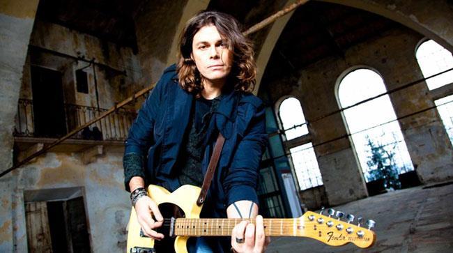 Gianluca Grignani con la chitarra in un capannone