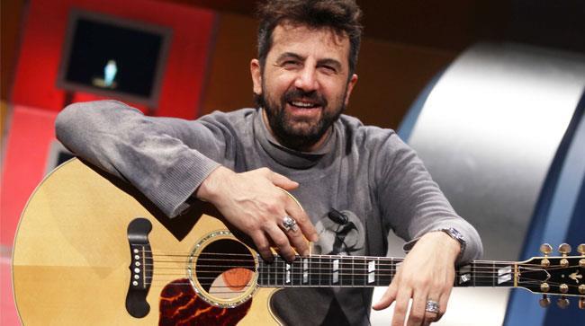 Omar Pedrini seduto con la chitarra in braccio