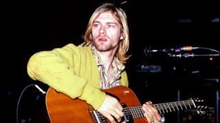 Kurt Cobain suona la chitarra durante un'esibizione dal vivo