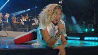 Emma Marrone canta sdraiata sul palco durante un concerto