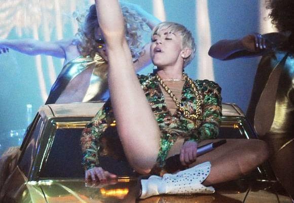 Miley Cyrus a gambe aperte con il microfono vicino alla vagina