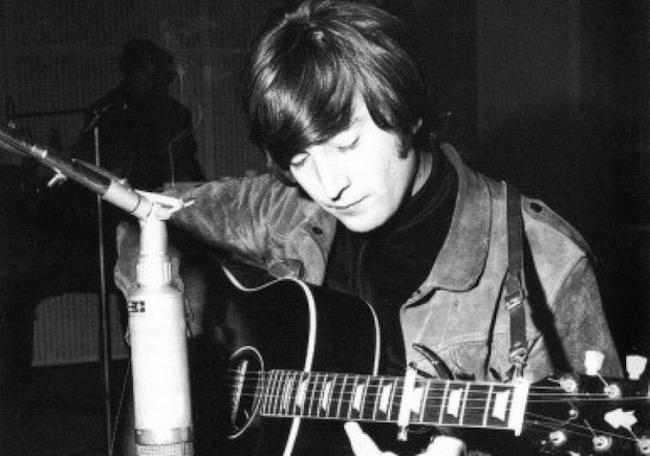 John Lennon con una chitarra acustica in mano