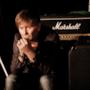 Ron seduto fra chitarre e amplificatori