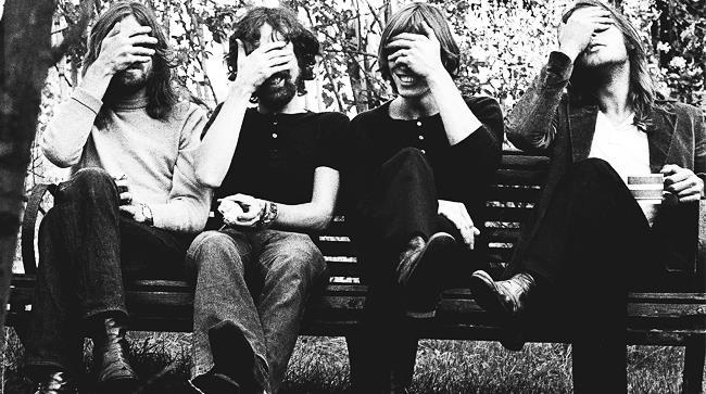 Pink Floyd che si coprono gli occhi seduti insieme su una panchina