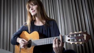 Carla Bruni con la chitarra in mano