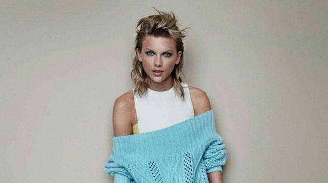 Taylor Swift con canotta bianca e maglione azzurro