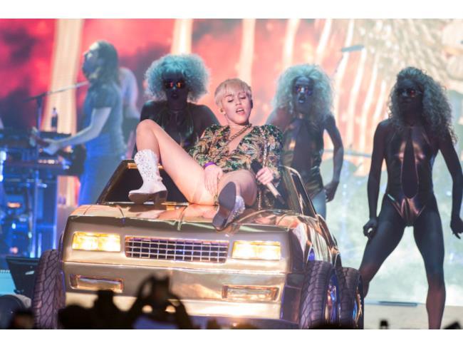 La Cyrus adagiata su una macchina si tocca i genitali