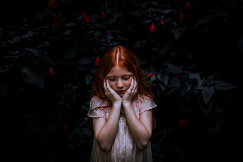 Bambina con le mani sulle guance preoccupata