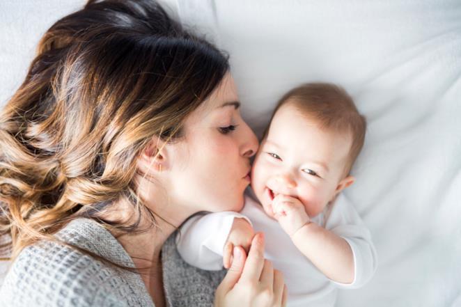 Una mamma bacia un figlio sulla guancia