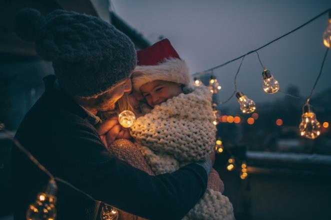 Un padre tiene in braccio la figlia tra le luci natalizie