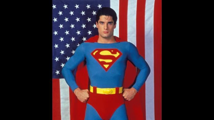 Mezzobusto di John Haymes Newton in costume da Superboy con bandiera americana sullo sfondo