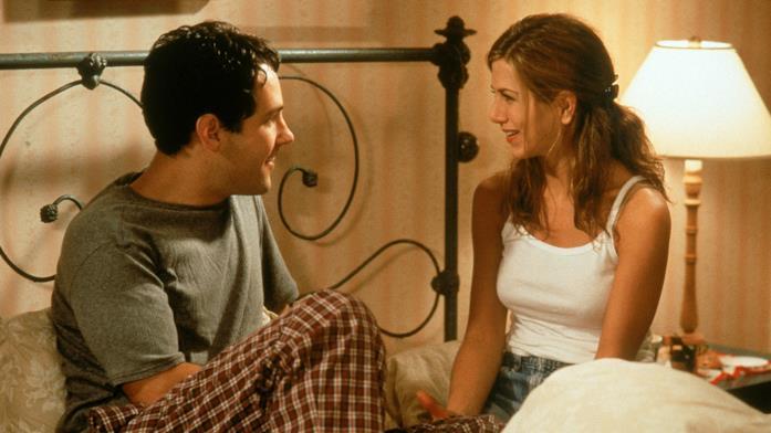 Paul Rudd e Jennifer Aniston conversano seduti su un letto