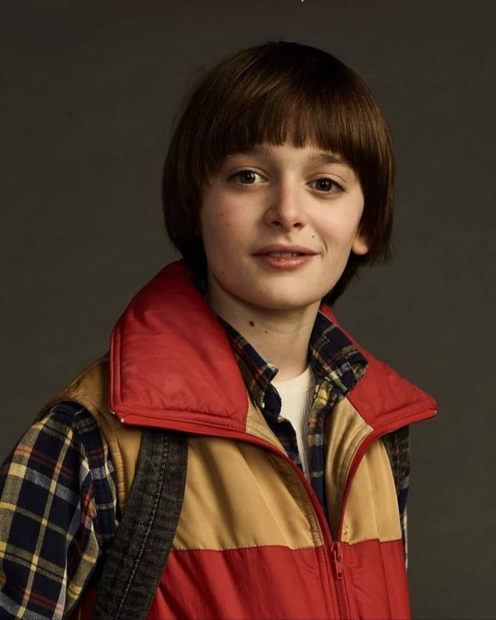 Noah Schnapp nei panni di un sorridente Will Byers, con giubbetto rosso e giallo, camicia e zaino