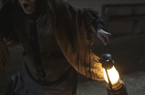 Una donna con una lampada scappa terrorizzata da un fantasma