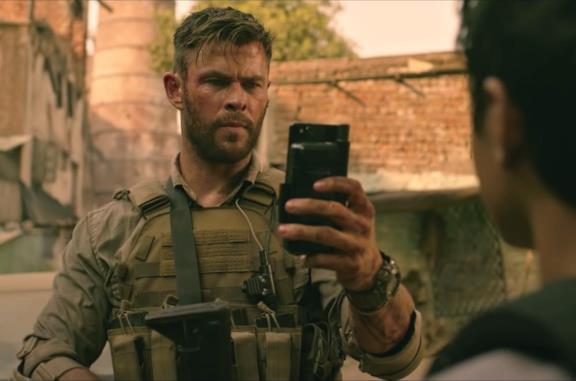 Mezzo primo piano di Chris Hemsworth accovacciato in una scena di Tyler Rake