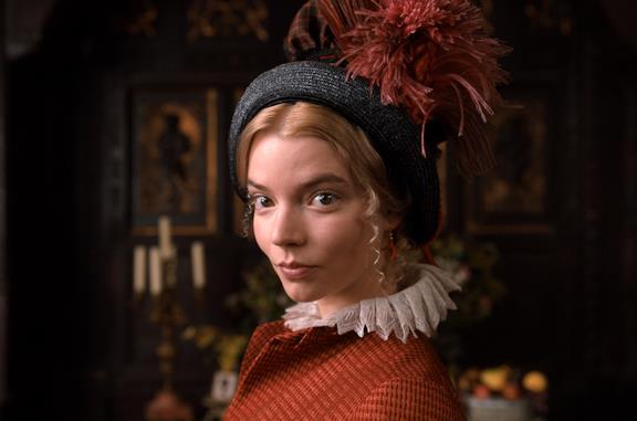 Emma guarda verso lo spettatore, vestita sui toni dell'arancione e blu