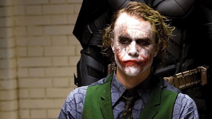 Joker (Heath Ledger) seduto ed alle sue spalle l'ombra di Batman (Christian Bale)