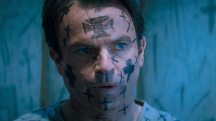 John Trent (Sam Neill) con la faccia ricoperta di croci in un manicomio