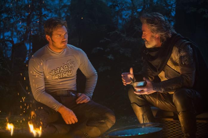 Peter Quill (Chris Pratt) ed Ego (Kurt Russell) seduti davanti ad un fuoco acceso in una scena del film