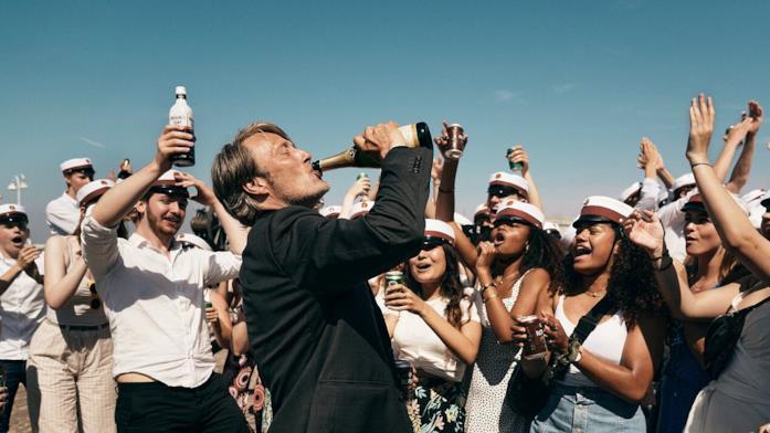 Martin beve a canna da una bottiglia di champagne