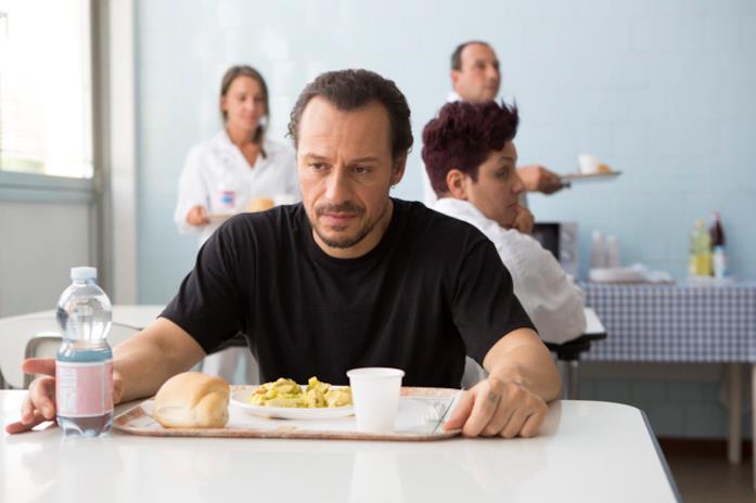 Stefano Accorsi seduto in mensa in Made in Italy