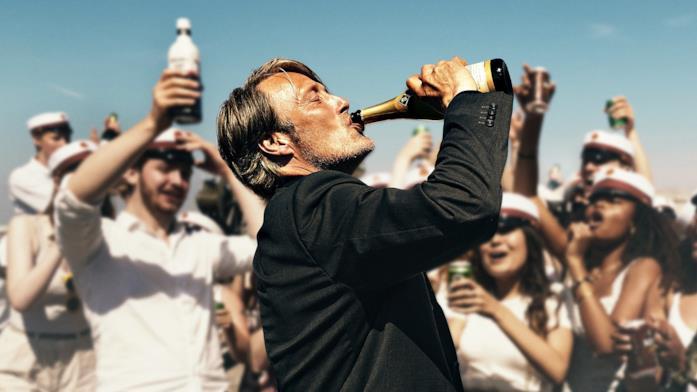 Martin beve dalla bottiglia circondato dagli studenti