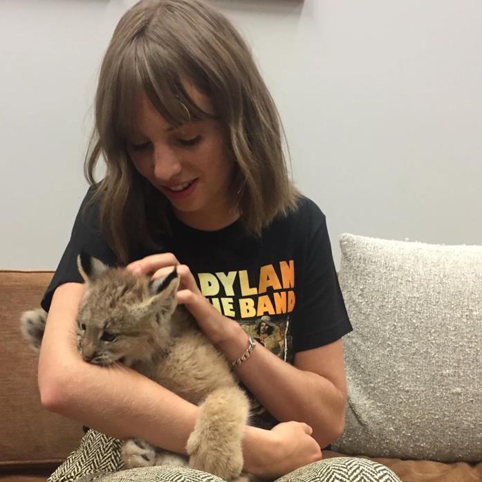 Maya Hawke seduta su un divano con un in braccio un leoncino