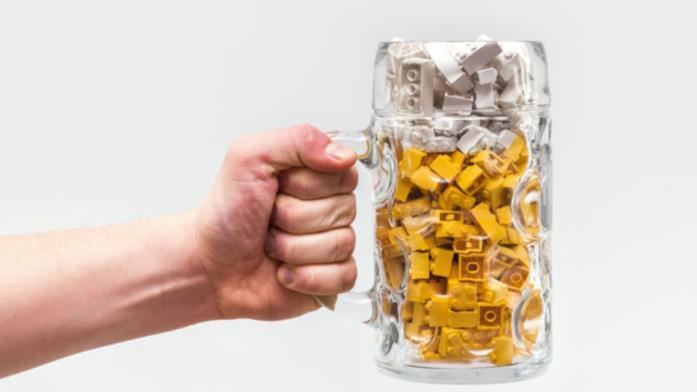 Primo piano di una mano che impugna un boccale di birra contenente mattoncini LEGO