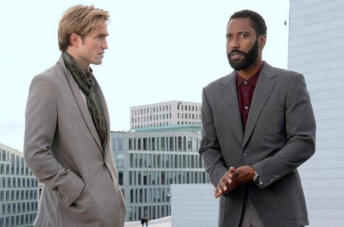 I due protagonisti del discutono attorniati da alti edifici