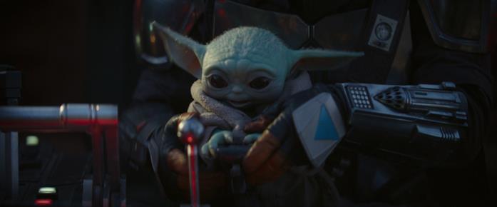 Baby Yoda e Mando in una scena della serie The Mandalorian