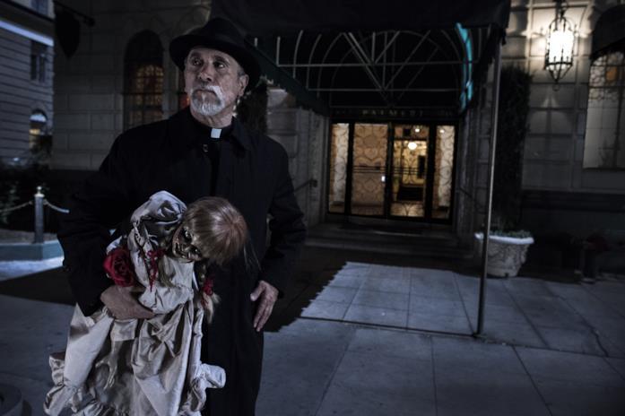 Padre Perez tiene in mano la bambola Annabelle