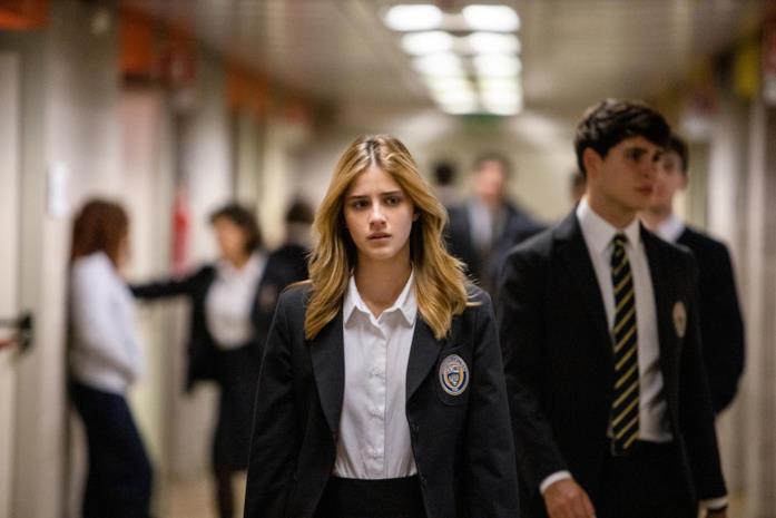 Chiara, visivamente preoccupata, cammina all'interno della propria scuola
