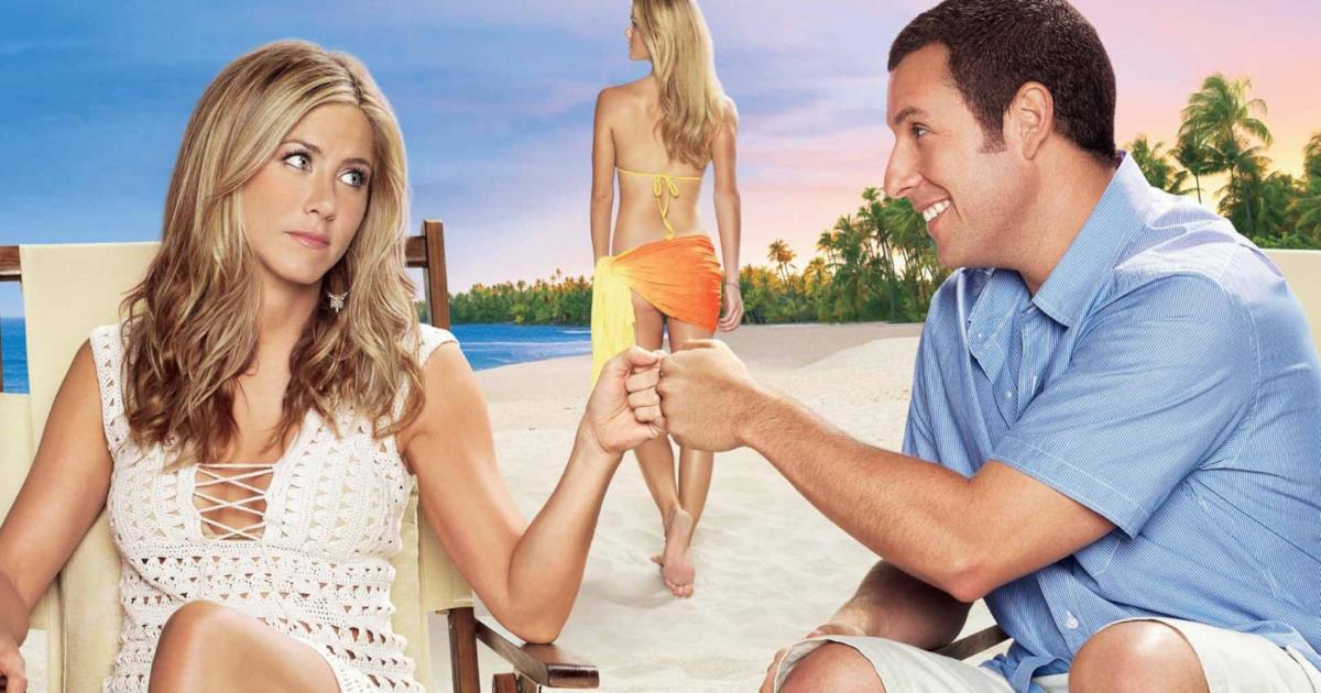 Locandina del cult estivo con Jennifer Aniston e Adam Sandler. I due sono seduti in spiaggia, si guardano e si scambiano un gesto d'intesa con la mano.