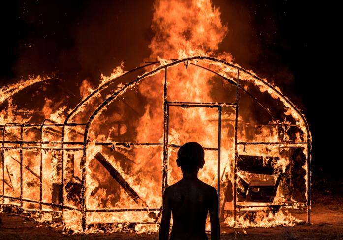 Un bimbo osserva la serra bruciare in una scena di Burning