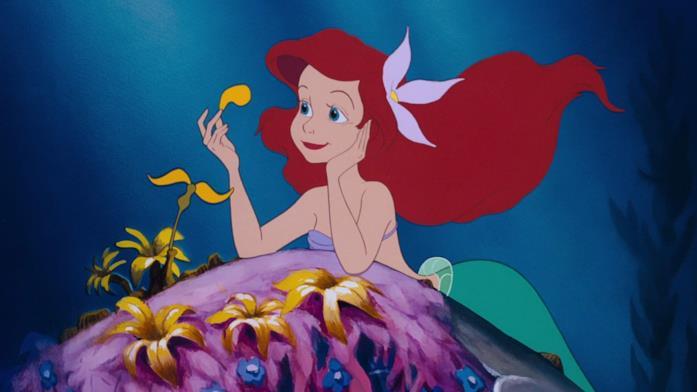 La sirenetta Ariel che contempla i petali di un fiore