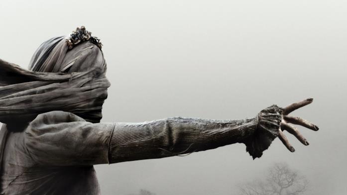 La llorona con il braccio teso verso qualcosa, in mezzo alla nebbia