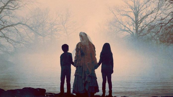 La Llorona, di spalle, conduce un bambino e una bambina verso un lago immerso nella nebbia